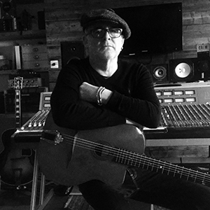 Black and whit eimage of Adrian wearing flat cap and dark glasses, leans on an acoustic guitar in front of a mixing desk