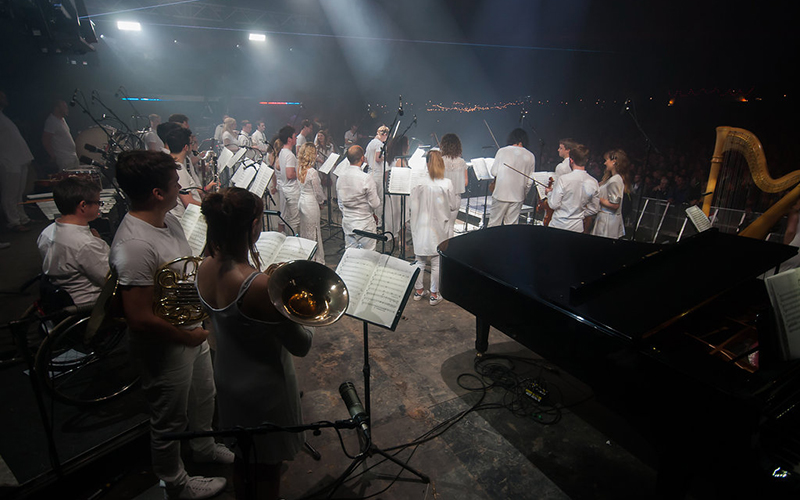 Army of Generals, photo taken from the back of the stage at Glastonbury, ensemble members holding instruments ready to play
