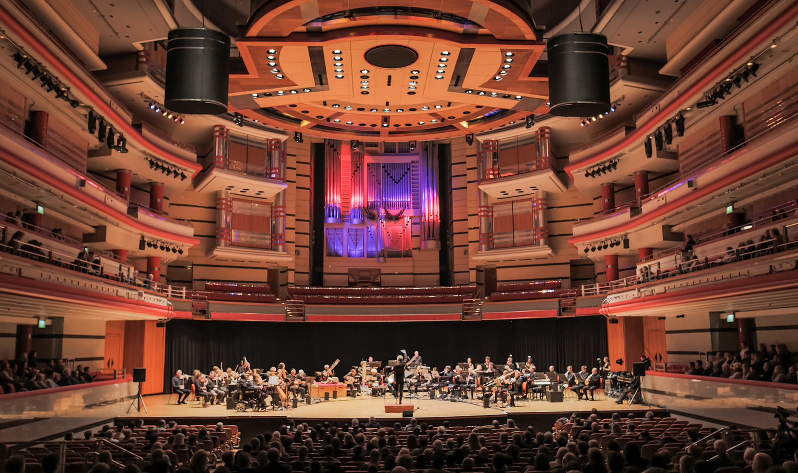 A long wide view taken from the back of the auditorium, of The British Paraorchestra playing on stage at the Birmingham Symphony Hall, audience members' heads can be seen at the forefront.