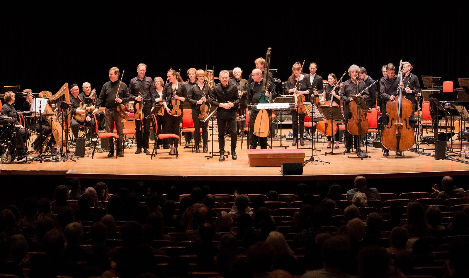 Photo of British Paraorchestra Birmingham on stage at Symphony Hall, full ensemble, Charles Hazlewood centre front
