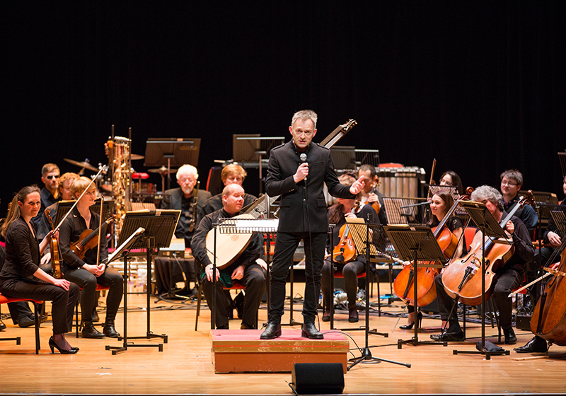 Charles Hazlewood and The British Paraorchestra at Birmingham Symphony Hall addresses the audience, musicians behind him dressed in black, smiling, ready to play