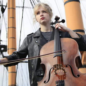 Hattie looks away from the camera and plays cello on what appears to be a tall ship, masts in the background