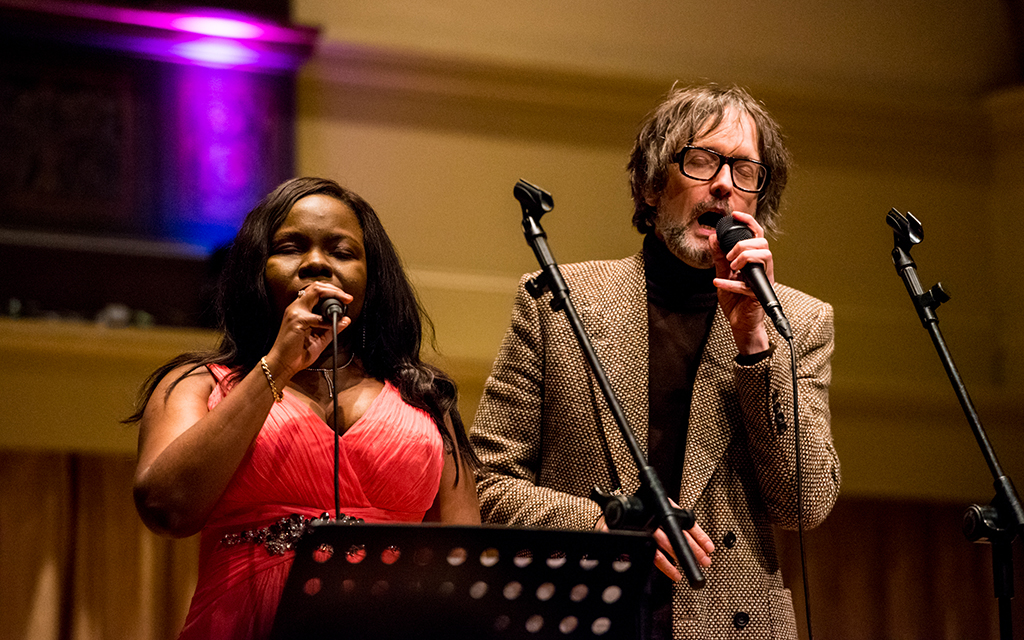 Victoria Oruwari, left, wears a read evening dress, sings into a microphone infront of a music stand. Karvid Cocker, right, beard, wearing tweed, sings.