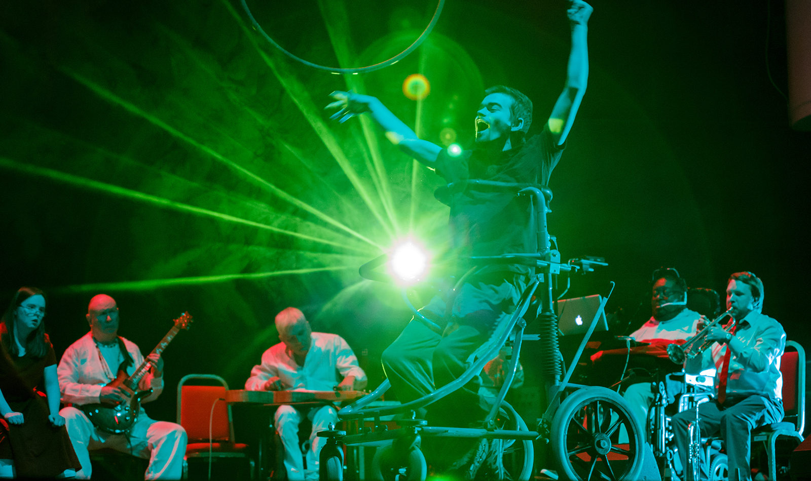 An Extraordinary Bodies company member performs in a wheelchair centre stage, members of the British Paraorchestra play their instruments behind him