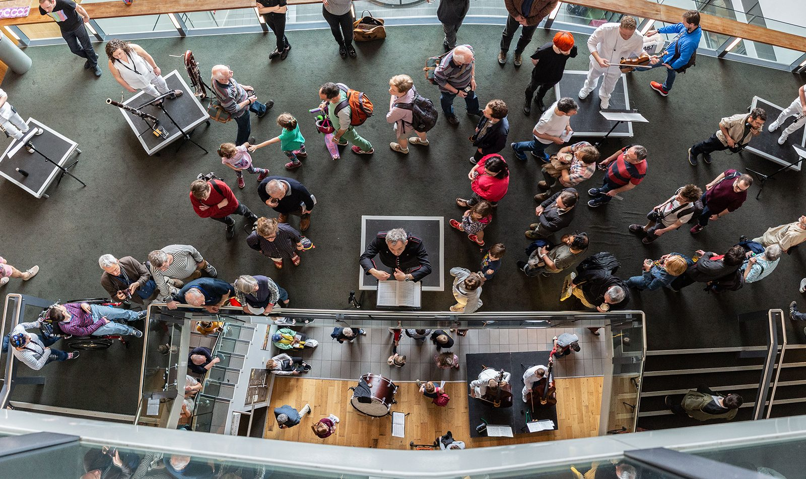 Taken from above, the top floor of the foyer at Colston Hall, looking down on Charles Hazlewood conducting musicisn spread out amongs the lower levels. Audienes wander between the musicians. Largle windo lights the scene from behind.