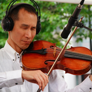 Takashi plays the viola in front of a microphone whilst wearing headphones