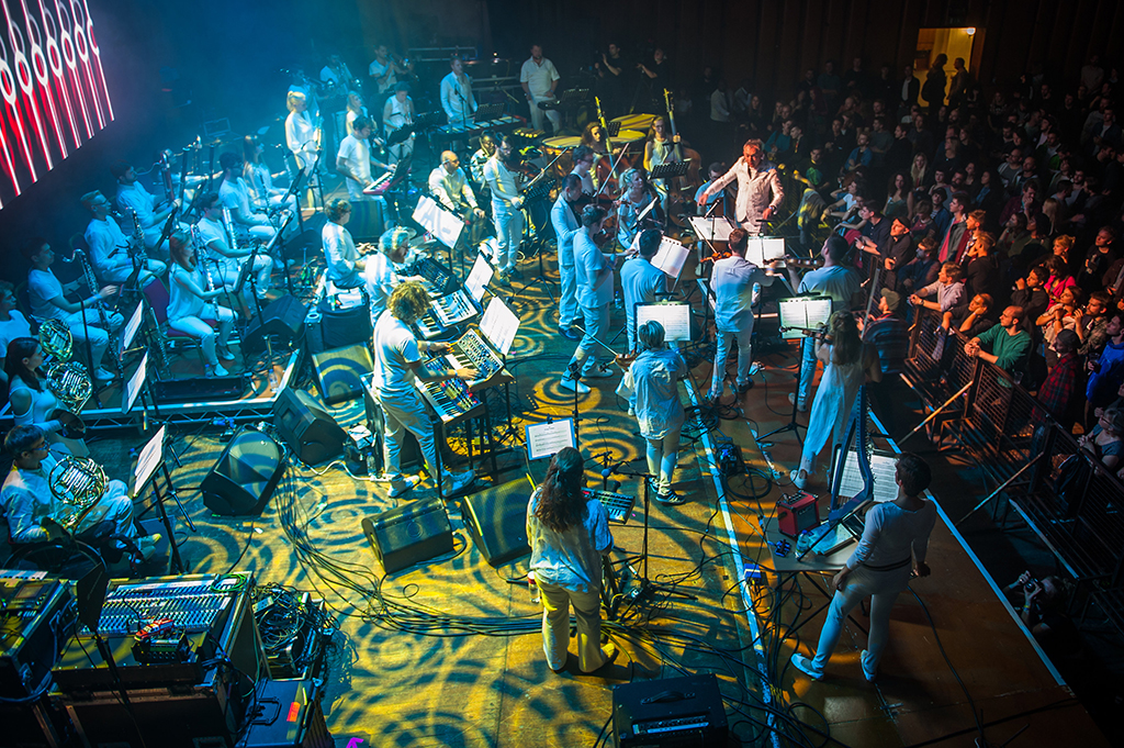 Side view of orchestra on stage at Colston Hall, brightly lit in blue and yellow hues. Graphics projected onto the stage in psychedelic circular patterns.