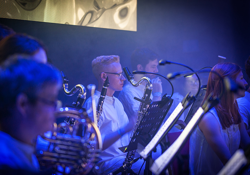 Side angle of musicians on stage, not playing, standing in front of music stands, we see a french horn, clarinet, and a bass clarinet. Some faces out of focus.