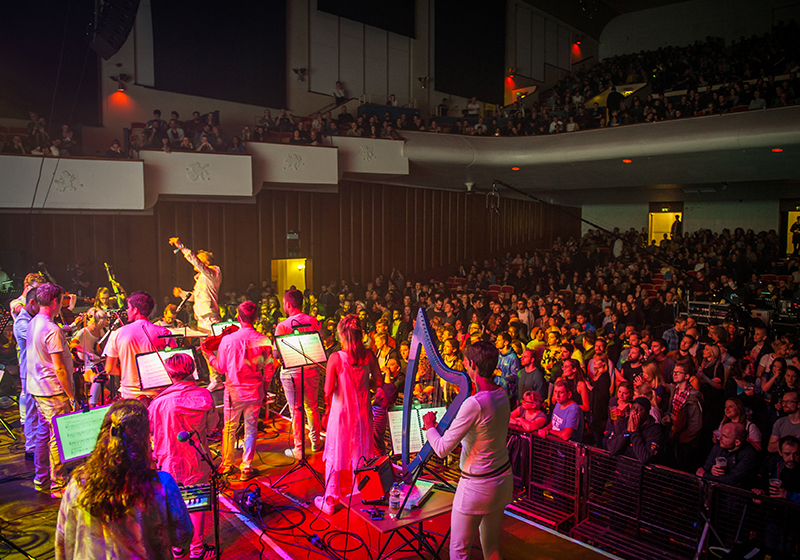 Taken from the rear corner of the stage, we see a full auditorium in partial darkness, musicians stood in front of their music stands and a harpist in the foreground