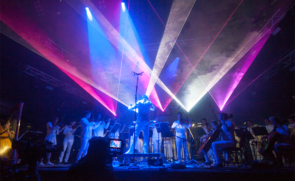 Charles Hazlewood conducts musicians on stage lasers in pink, whites and blues light the stage with dramatic effect