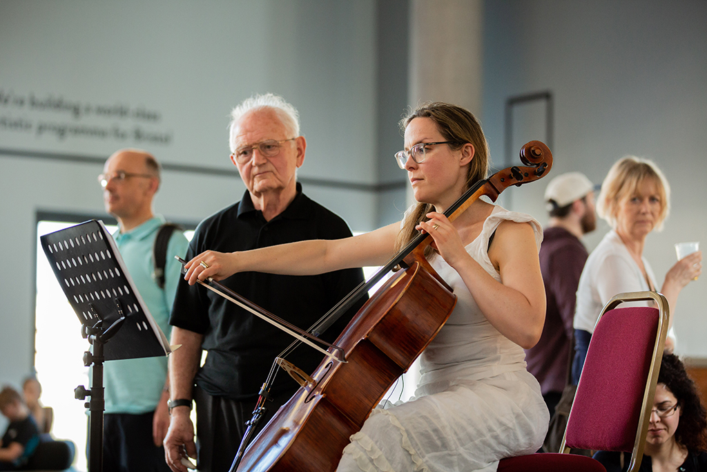 A mature man looks over the shoulder of a younger female cellist as she plays