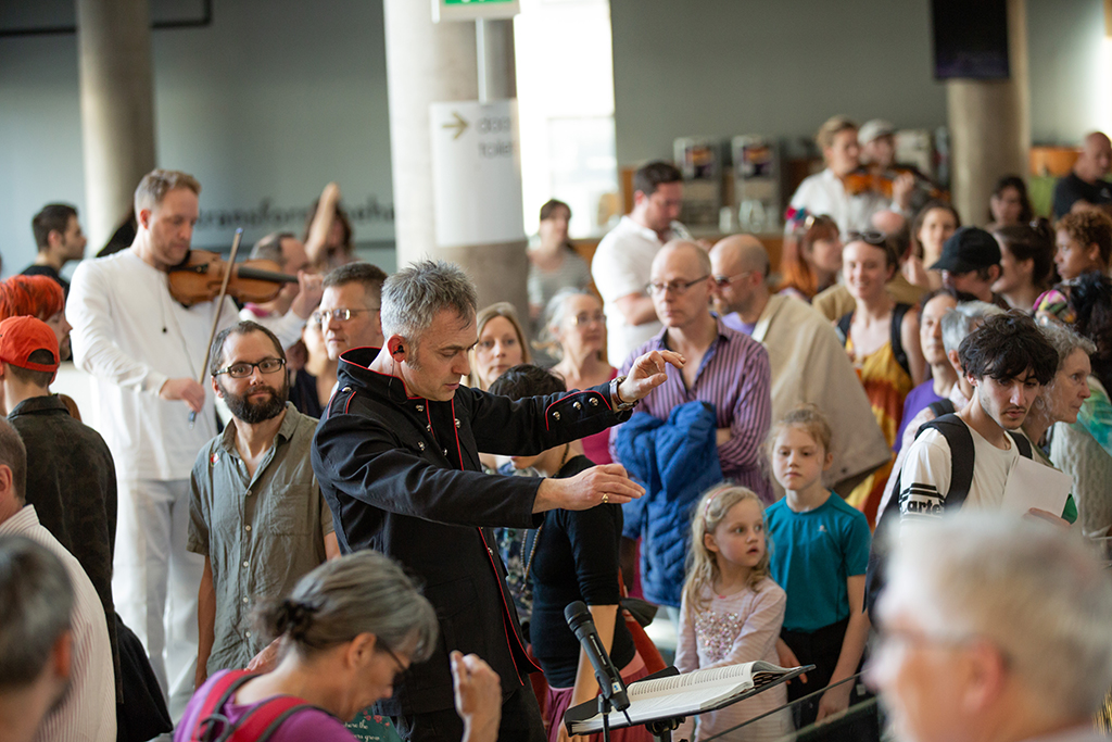 Charles Hazlewood conducting is surrounded by members of the public of all ages someof whom are watching Charles, others looking at unseen action elsewhere