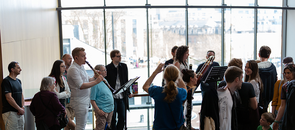 Audience members photograph a clarinettist and bassoon player in front of the windows at Colston Hall as they play.