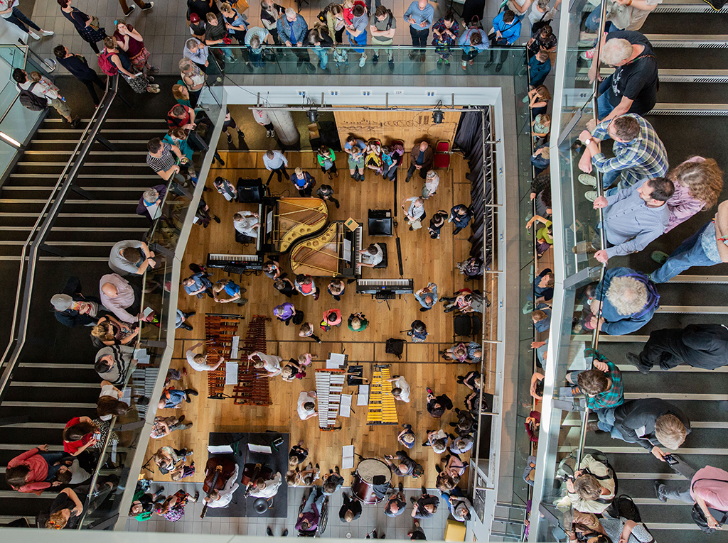 An aerial shot takes in Colston Hall's foyer staircase showing musicians and member sof the orchestra spread out across all levels.