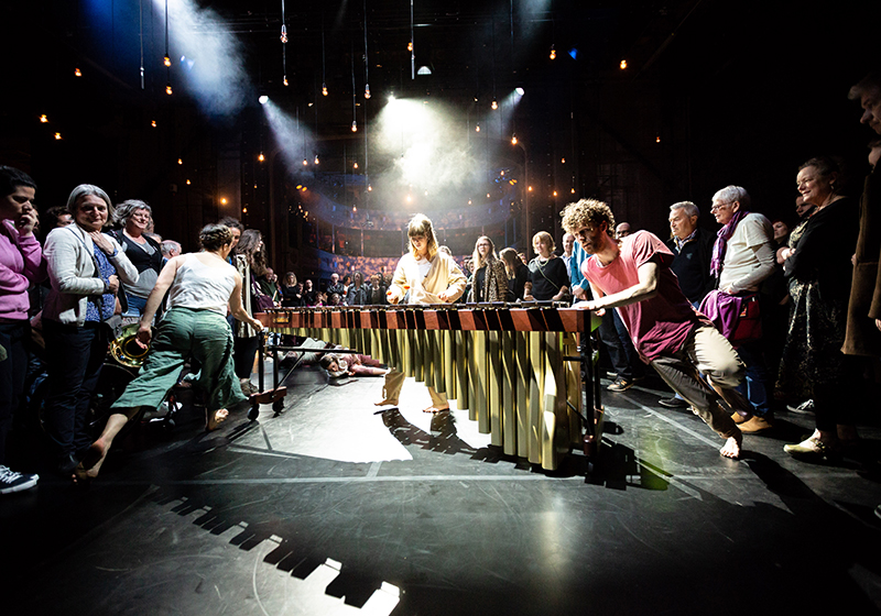 Two dancers turn a marimba round and round, one on each end whilst a percussionist plays, audience all around