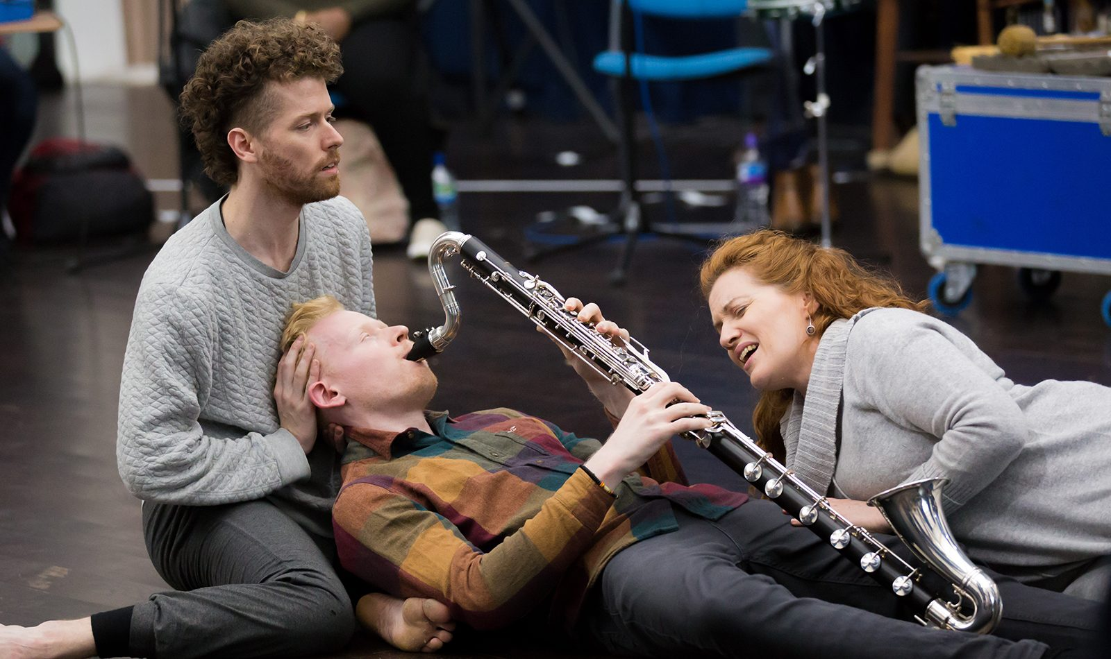 On the floor of a rehearsal room, two dancers and a clarinet player interact
