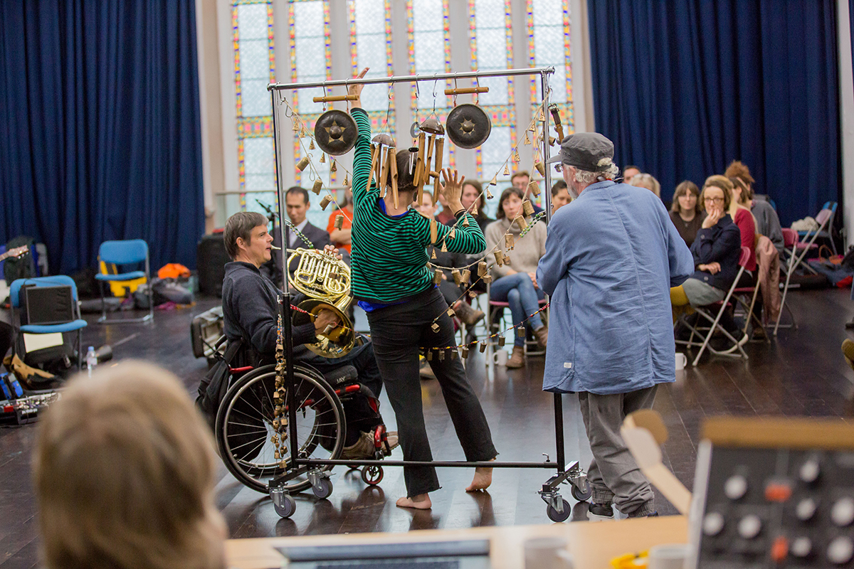 A horn player and a percussionist play as a dancer mingles amongst the percussion.