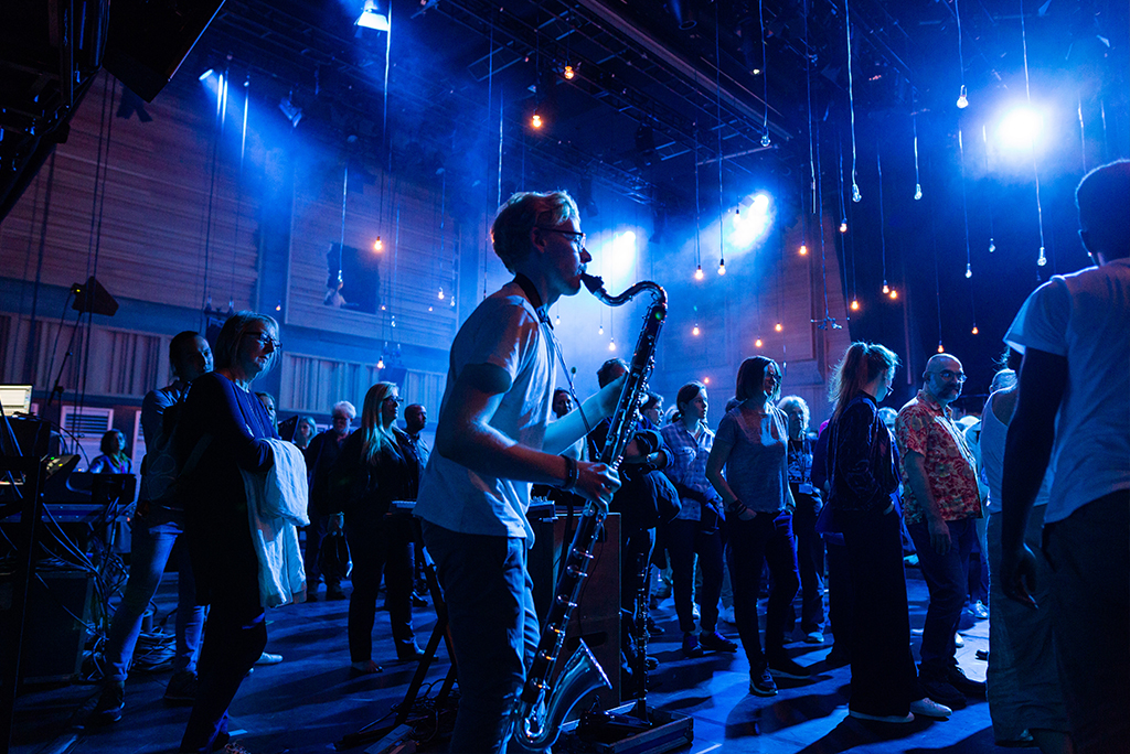 Under twinkling hanging lights a man plays an alto clarinet on a stage surrounded by audience members. Atmospheric blue and white lighting