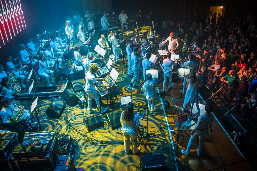 taken from above stage right showing full orchestra lit by psychedelic lights, patterns of yellow and blue across musicians and stage