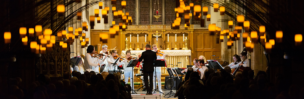 Wide view of Church interior, silhouettes of congregation, warm lights hang from the ceiling. At the front string players in white play, Charles Hazlewood conducting.