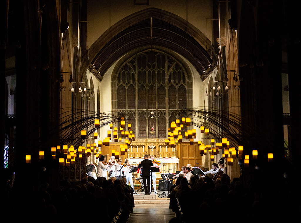 Portrait view of Church interior, silhouettes of congregation, warm lights hang from the ceiling. At the front string players in white play, Charles Hazlewood conducting.