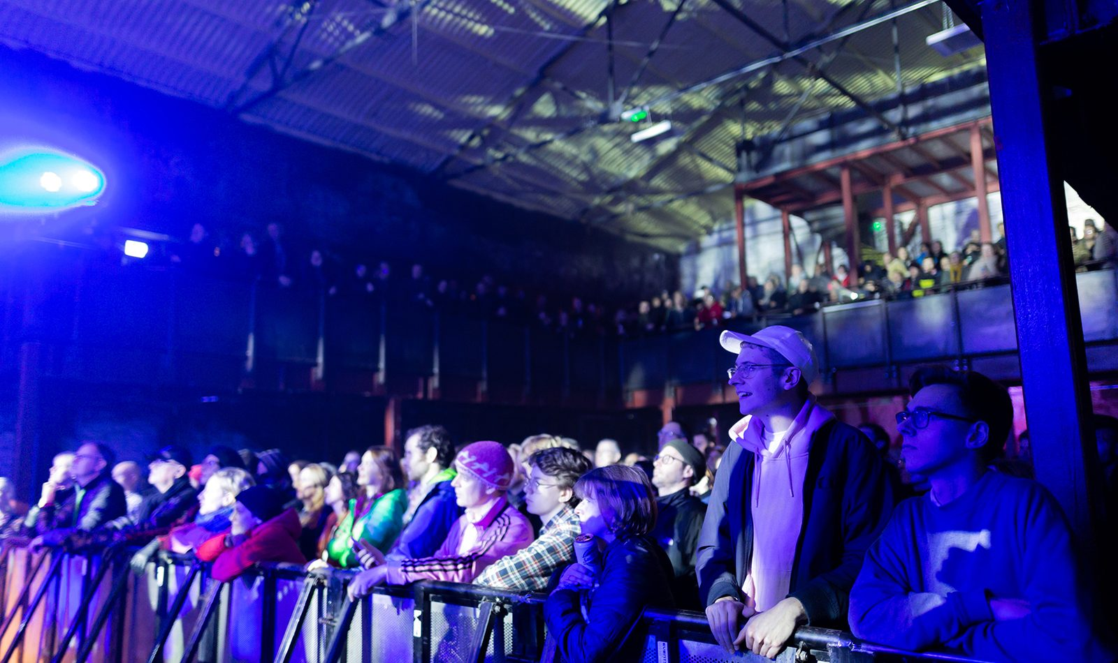 A gig crowd in a warehouse setting, dark, blue lighting, the standing audience watches an unseen stage