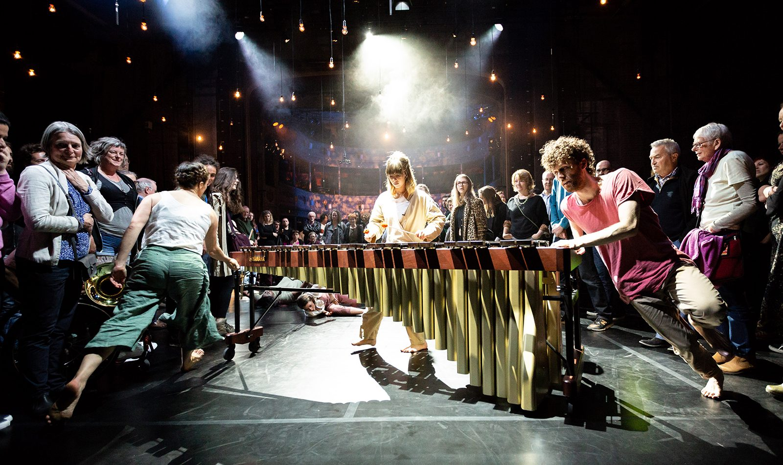 A female musician plays the marimba on stage, a male and a female dancer twirl it around from either end. Audience on stage look on.