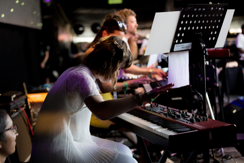 A female synthplayer, head down over her instrument hands raised mid-play