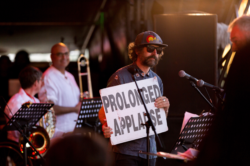 Gruff holds a sign that says 'Prolonged Applause' on stage. music stands in the foreground
