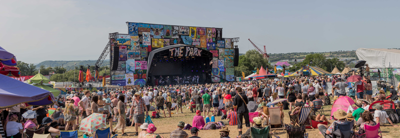 wide shot of the park stage glastonbury, crowd in the foreground, the ensemble onstage in the distance