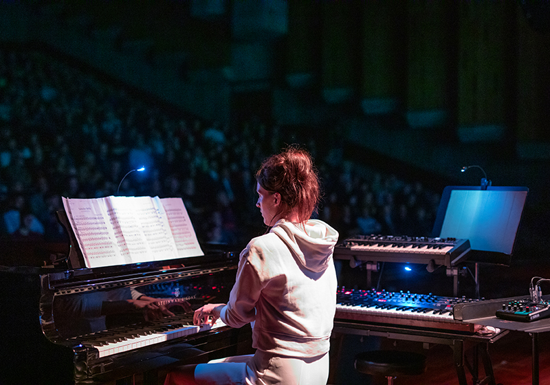 a keyboard player plays with her back to the camera, audience in the background