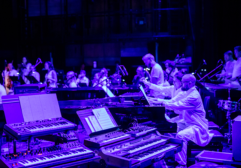 keyboards on stage, musicians in the background, purple lighting