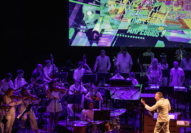Large Orchestra play on a dimly lit stage, purple lighting, conductor leads from the front, a large screen behind displays psychedelic images