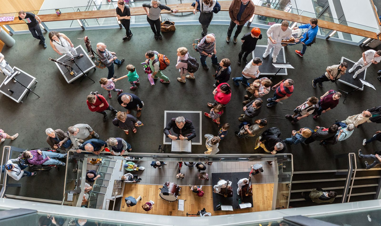Aerial photo of a conductor, musicians play behind whilsyt audiences wander around them