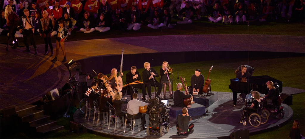 A dozen musicians perform in a circle, outdoor, celebratory setting