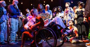 A dancer crouches low, supporting a wheelchair thats tipped up on two legs. Man in wheelchair plays the horn