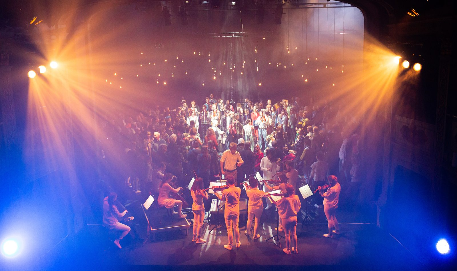 Looking down on a stage lit with blue and yellow, string players, conductor and audience mill in the background