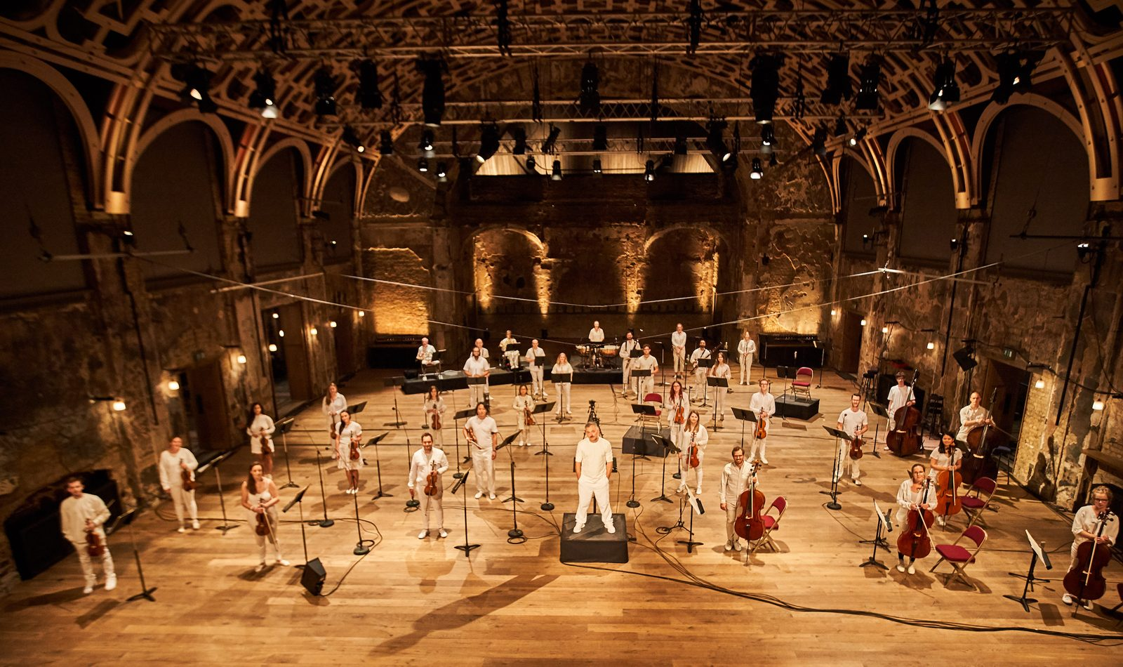 An orchestra in white spread aout across the floor of a arched hall