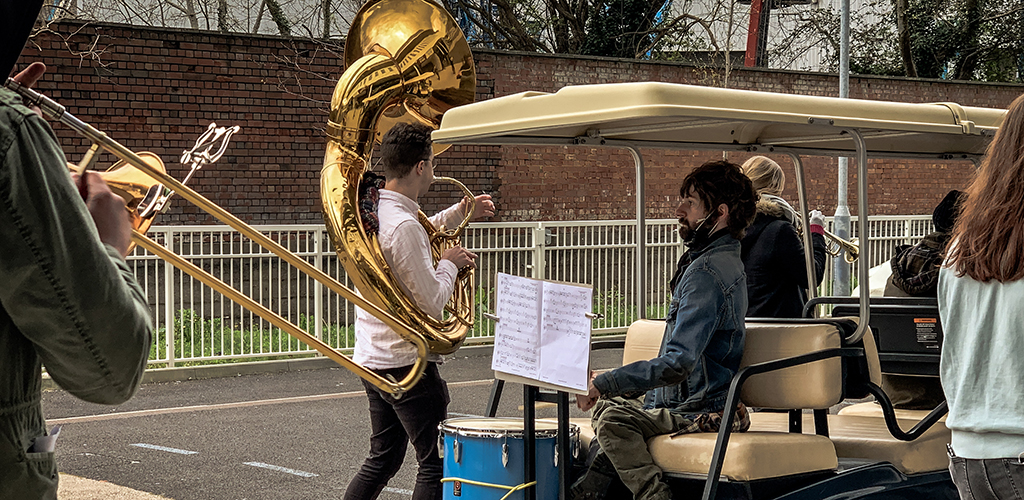 Outside, a trombone player in the foreground, a sousaphone player, a drummer plays drums mounted on the back of a golf buggy
