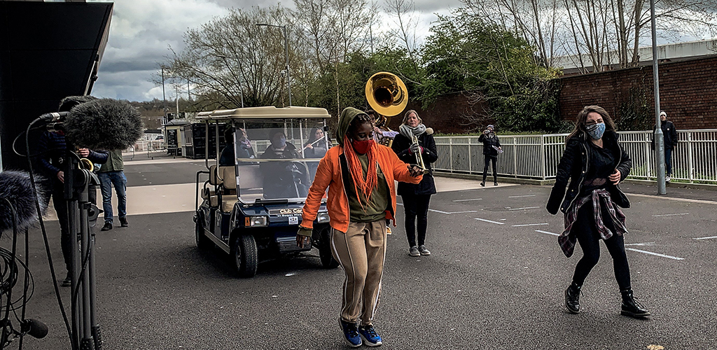 Outside, two dancers perform on the move. A golf buggy and a sousaphone in the background.