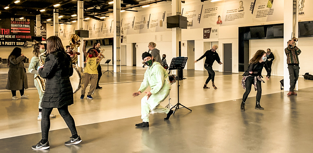 Dancers and musicians rehearse in a large indoor concourse. Socially distanced.