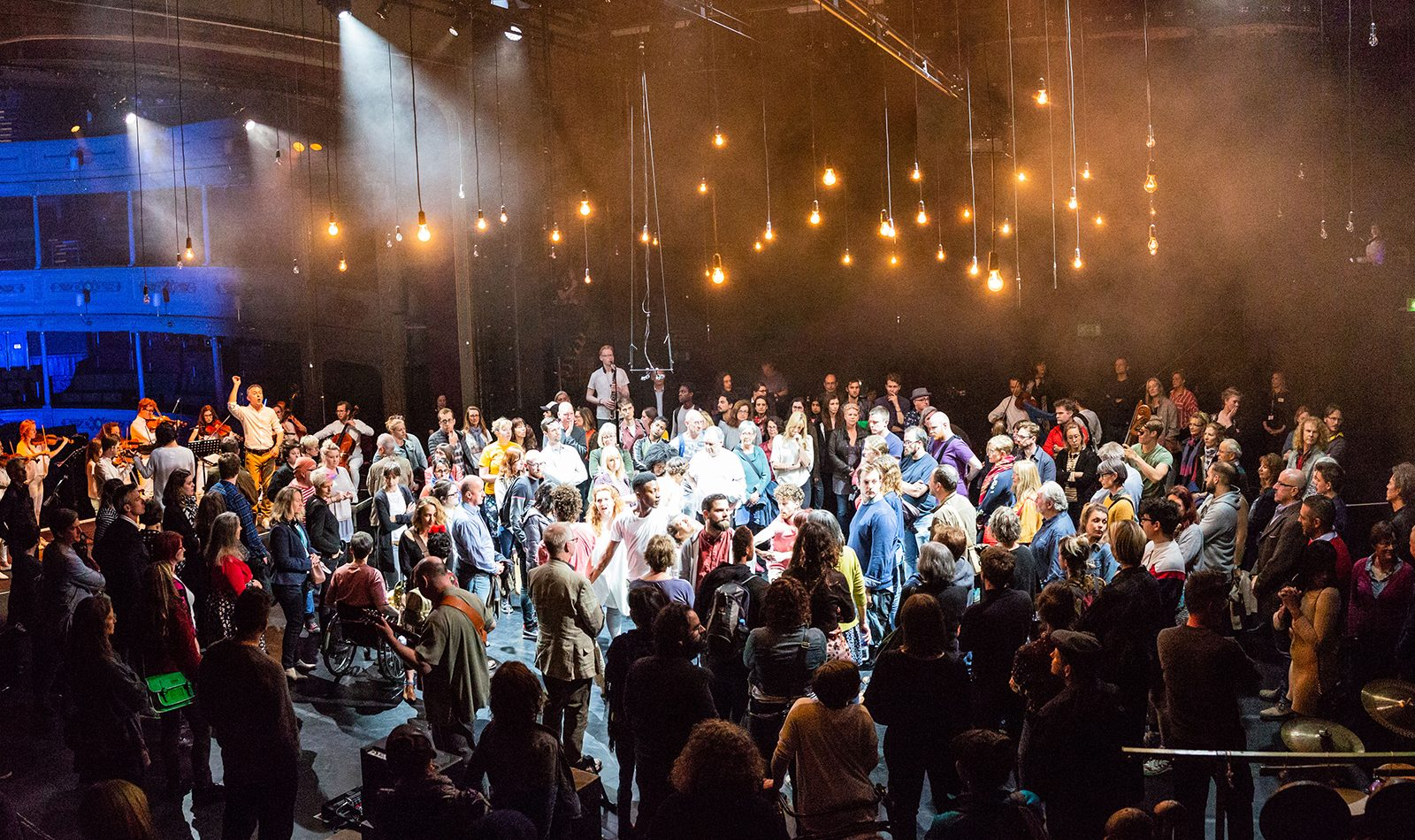 An audience and performers on stage blub lighting hangs from the ceiling