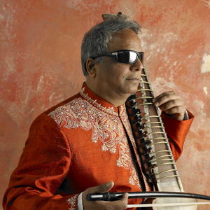 Baluji plays the dilruba, turned slightly to the right.