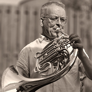 sepia photo, chris in white shirt plays french horn