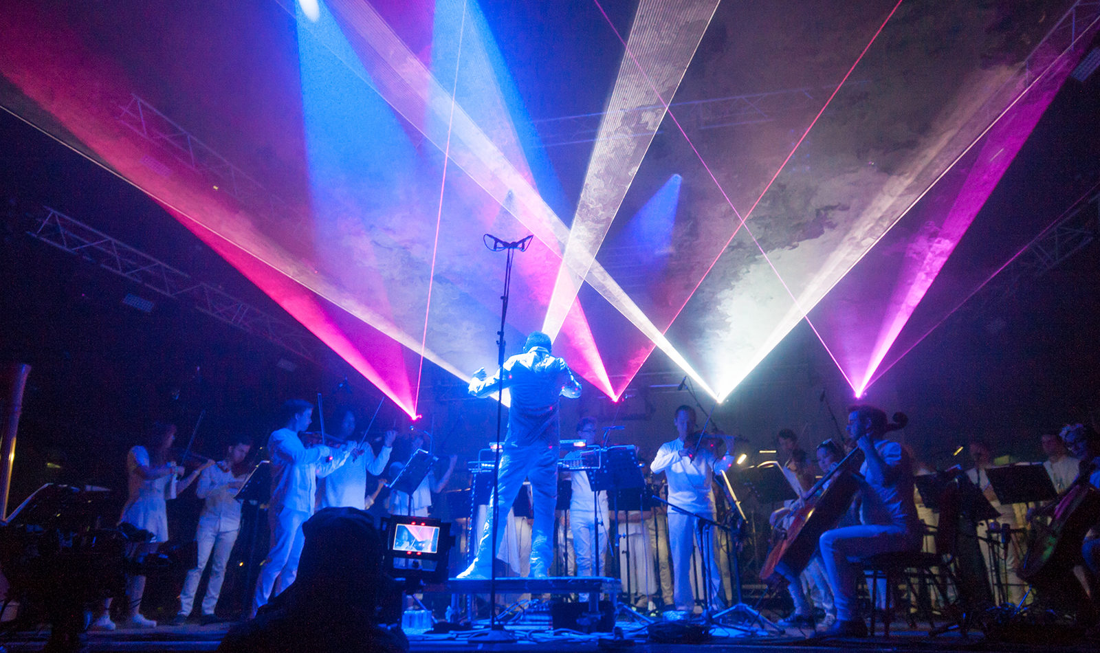 Charles Hazlewood conducts an orchestra all dressed in white. Bright lasers appear to project out of the ensemble above.