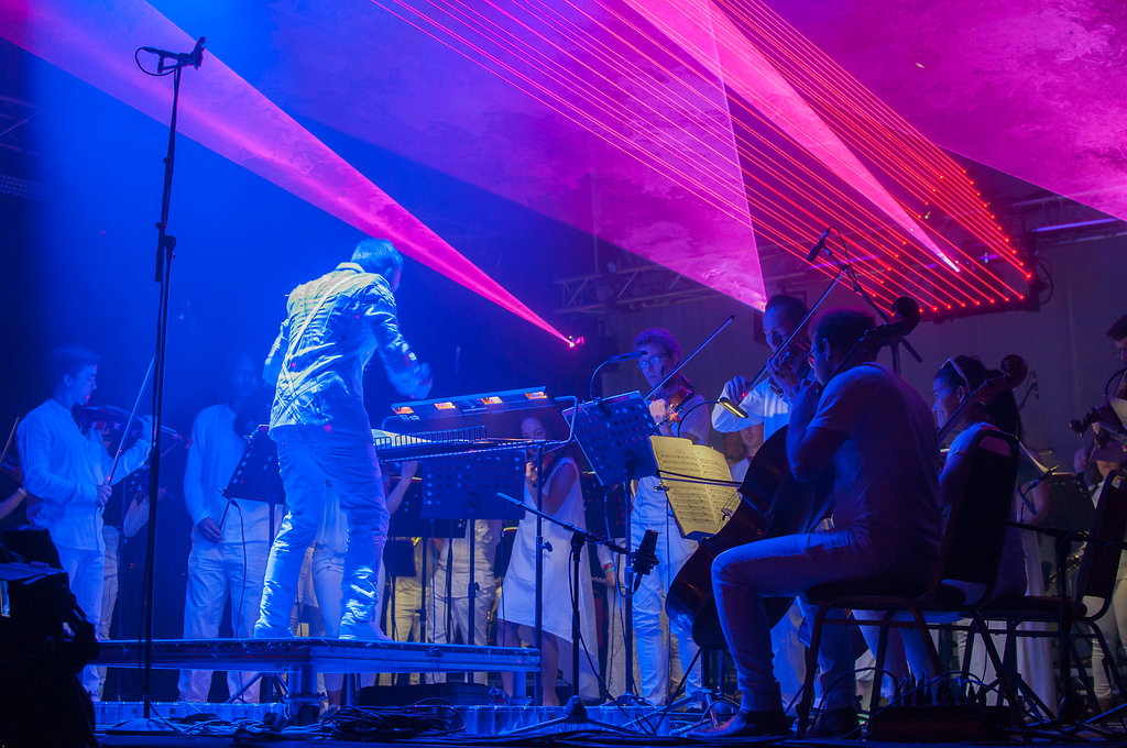 Charles Hazlewood conducting the full orchestra on stage at Glastonbury for the Heroes show, blue and pink lasers fill the top of the image