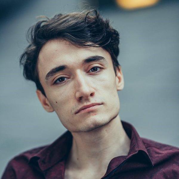 Jonathan looks at the camera. He has dark hair and a maroon shirt.
