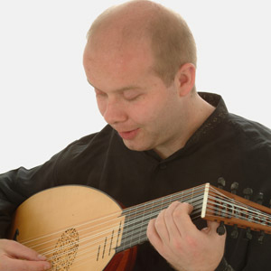 Matthew plays the lute, looking down at the instrument as he plays