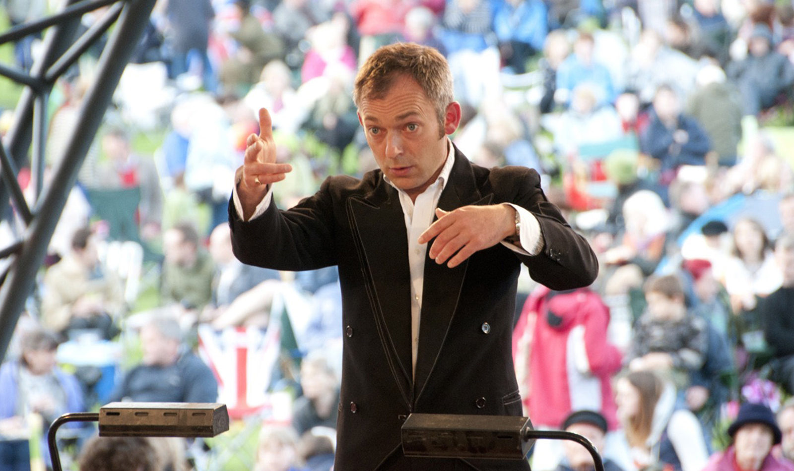 Charles Hazlewood conducting, a blurred crowd in a field in the foreground
