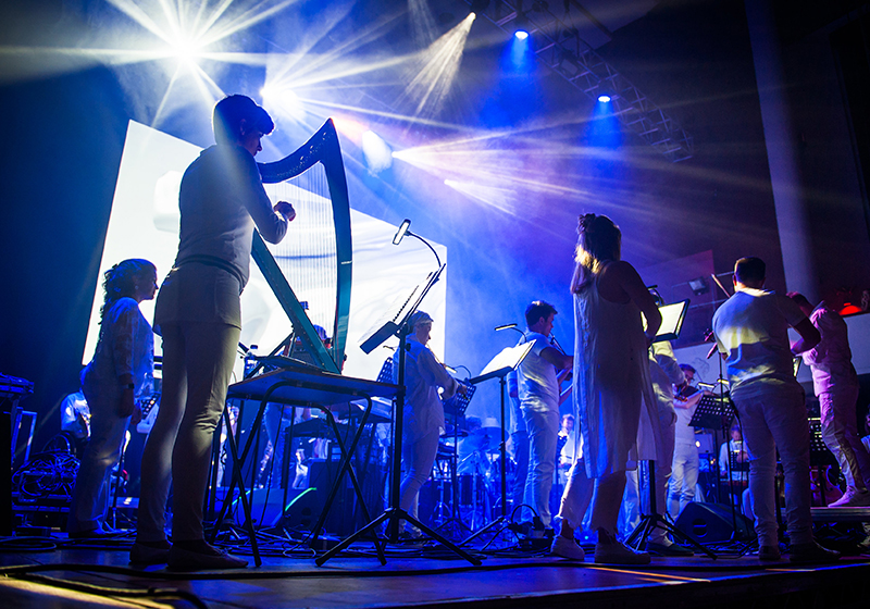 On stage, back rea angle of the musicians playing, harpist in the forefront, blue and purple lighting